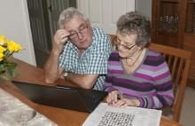 Elderly couple playing a crossword puzzle