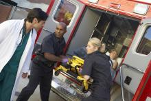 EMTs and doctor unloading patient from ambulance