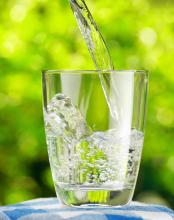 Filled water glass against outdoor background