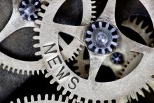 Interlocking gears with the word News imprinted