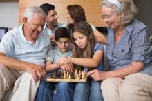 Grandparents sitting with two kids playing chess while parents sitting in the background talking