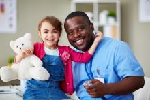 Young girl hugs her teddy bear and healthcare provider