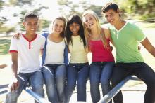 Five teens sitting on a fence with arms around each other