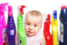 Smiling baby sitting with cleaning products
