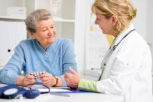Doctor consults with elderly woman regarding medications