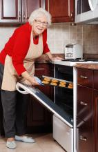 Elderly woman pulling tray from oven
