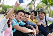 "Teens taking a ""selfie"" picture together outside"
