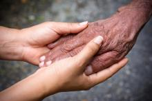 Elderly hand being held by younger hands