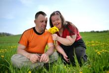 Adults with disabilities outdoors picking flowers