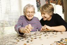 Elderly woman and daughter working on a puzzle