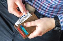 Adult holding wallet showing a ForwardHealth card.