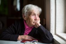 Sad older adult looking out a window
