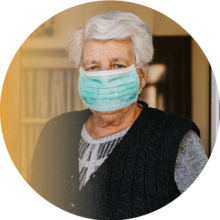 Circular image of an older woman in a face mask