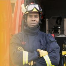 A firefighter in full gear standing with his arms crossed