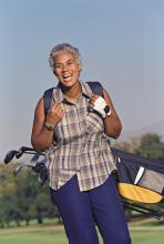 A smiling adult carrying a golf bag.