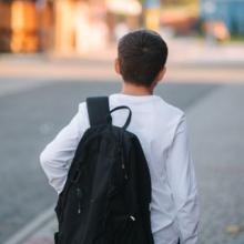 Child with backpack walking down street