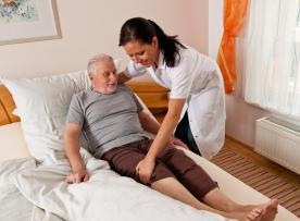 Caregiver readjusting reclined male patient