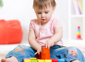 Cropped of toddler playing with blocks on the floor at home