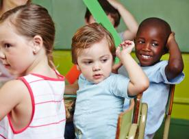Three young children at school table.