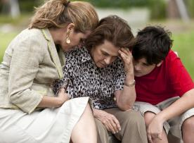 Upset adult receiving support from another adult and a teen outside.