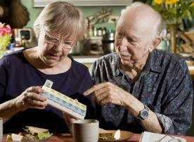 Elder couple sorting medications into daily organizer