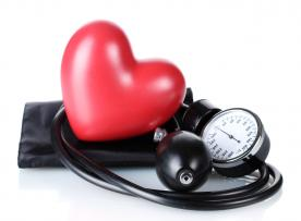Blood pressure monitor set with a plastic red heart on top of the cuff