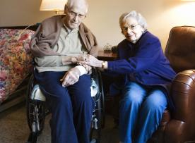 Seated older couple looking at camera