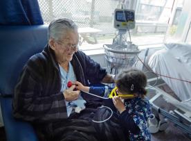 Toddler visiting elderly man at healthcare facility