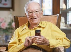 Smiling seated senior holding a mobile phone at home