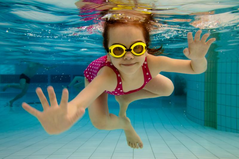 A happy child swims under water in a pool.