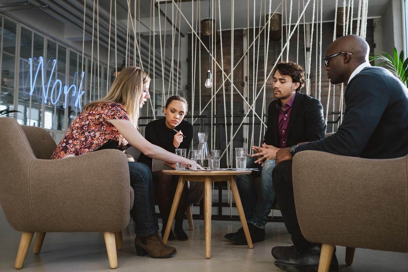 Image of people in a modern work setting collaborating around a table.