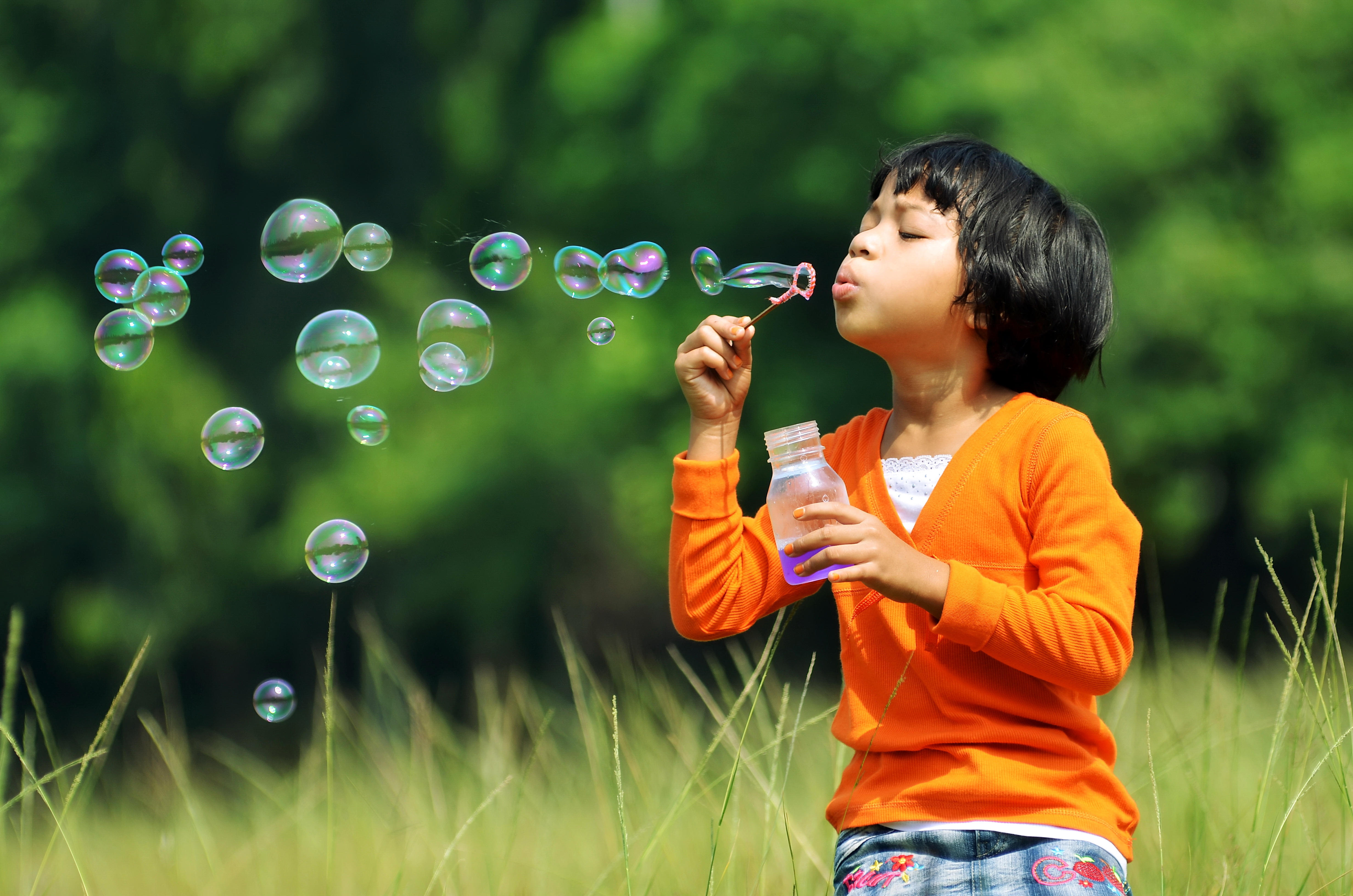Young girl plays while blowing bubbles outside